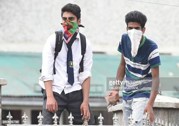 Kashmiri students throw stones during clashes with Indian government forces in central Srinagar's Lal Chowk on May 9 2017 Police fired into a crowd...