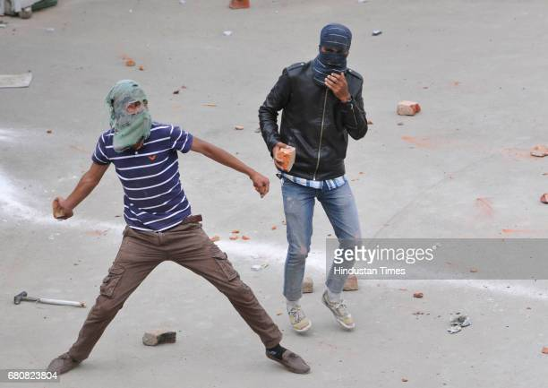 Kashmiri students throw stones during clashes with police at Lal Chowk on May 9 2017 in Srinagar India Clashes broke out between school students and...