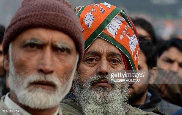 Kashmiri supporters of Indian Prime Minister Narendra Modi look on as he speaks during an election rally at a stadium in Srinagar on December 8 2014...