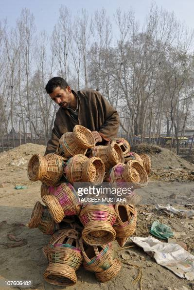 A Kashmiri vendor arranges 'Kangir' traditional Kashmiri fire pots at a market in Srinagar on December 8 2010 With the arrival of winter in the...