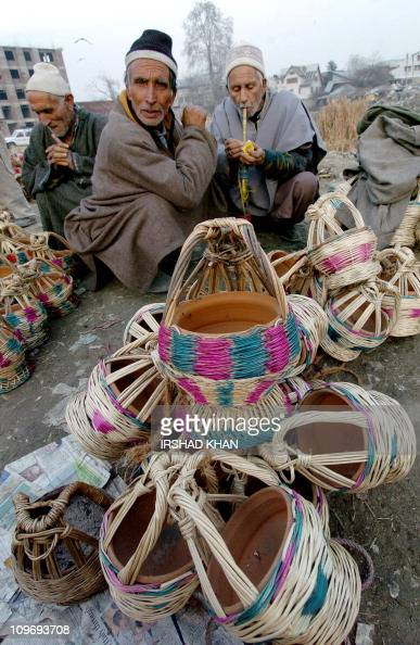 Kashmiri vendors smoke a hookah pipe as they wait for customers for their stock of traditional fire pots made to be carried under a woolen outer coat...