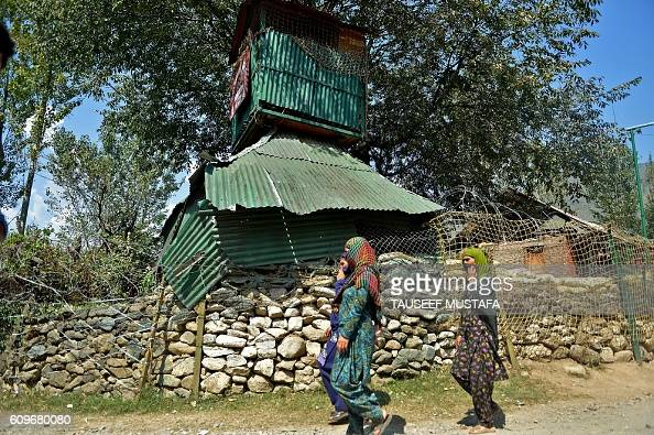 Kashmiri village women walk past an Indian army camp after an encounter between army soldiers and suspected militants at Aragam village of Bandipora...