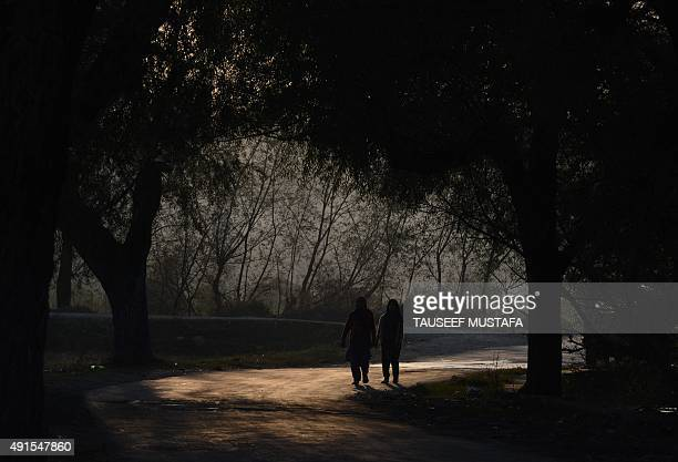 Kashmiri village women walks after working in a rice field on the outskirts of Srinagar on October 6 2015 Agriculture and horticulture are the main...