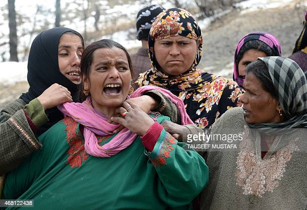 A Kashmiri villager cries as she stands with others during rescue efforts following landslides due to heavy rainfall in the village of Laden at...