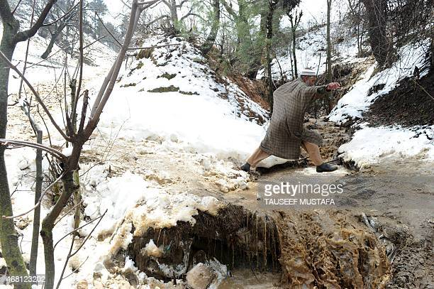 A Kashmiri villager jumps over the waters of a swollen stream in the village of Laden at Chadoora some 40kms west of Srinagar on March 30 2015...
