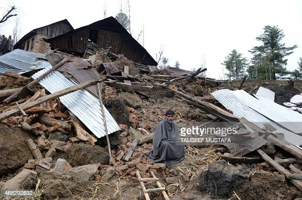 A Kashmiri villager sits near damaged houses following landslides due to heavy rainfall in the village of Laden at Chadoora some 40kms west of...