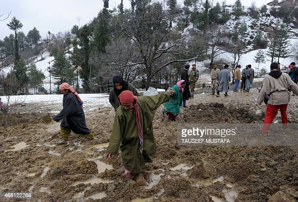 Kashmiri villagers and officials on muddy ground following landslides due to heavy rainfall in the village of Laden at Chadoora some 40kms west of...