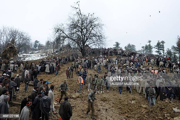 Kashmiri villagers and officials search for bodies following landslides due to heavy rainfall in the village of Laden at Chadoora some 40kms west of...