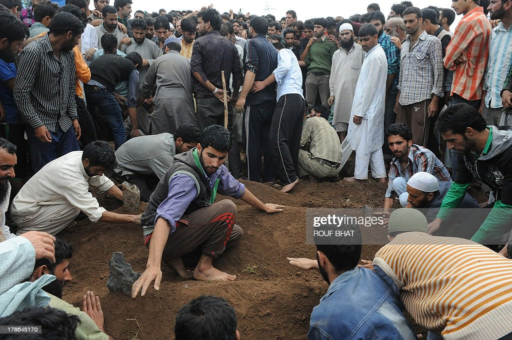 Kashmiri villagers bury the bodies of suspected militants during a funeral at Kangan on August 30, 2013. Indian police and troops killed five suspected rebels in an overnight gun battle August 30 in a forested area of northern Kashmir, triggering anti-India protests by local residents, police said. Police and an army contingent began a joint operation around midnight near the Najwan forests, 35 kilometres (20 miles) north of Srinagar, the summer capital of Indian-administered Kashmir. AFP PHOTO/Rouf BHAT