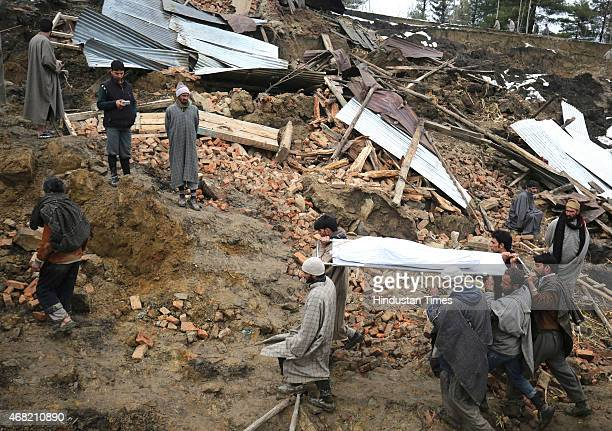 Kashmiri villagers carry body for a funeral in the village of Laden at Chadoora on March 31 2015 some 40kms west of Srinagar India Emergency workers...