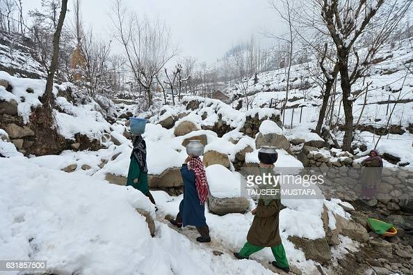 TOPSHOT Kashmiri villagers carry drinking water containers as they walk along a snow covered path on the outskirts of Srinagar on January 13 2017 A...