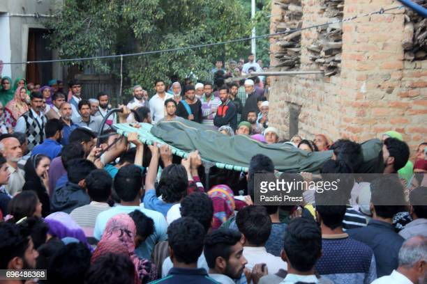 Kashmiri villagers carry the body of slain policeman Shabir Ah Dar killed by suspected militants on Thursday at village Bogund in Kulgam District