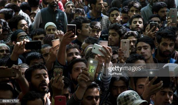Kashmiri villagers click pictures with their mobile phones during the funeral of a teenager Adil Magray at Shopian about 60 kilometers south of...