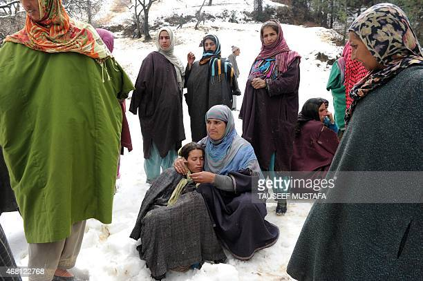 Kashmiri villagers gather during rescue efforts following landslides due to heavy rainfall in the village of Laden near Chadoora some 40km west of...