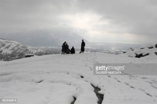 TOPSHOT Kashmiri villagers look from the top of a hill on the outskirts of Srinagar after a heavy snowfall on January 27 2017 / AFP PHOTO / Tauseef...
