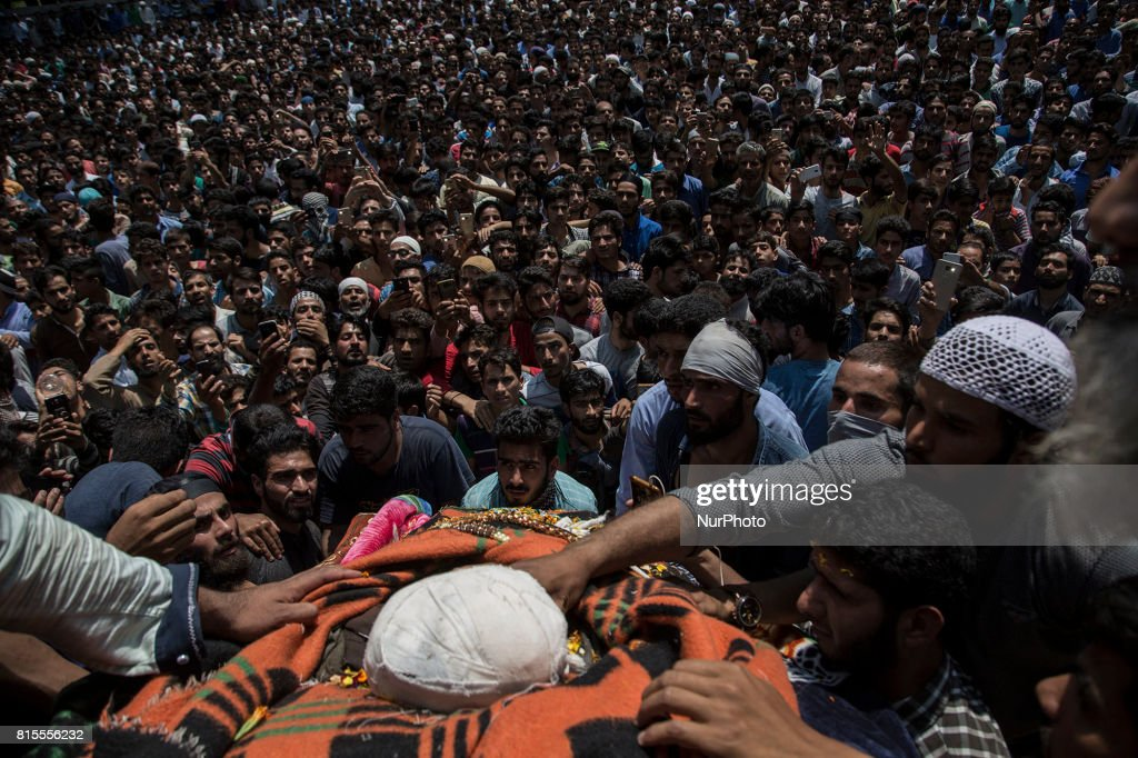 Kashmiri villagers touch the body of a local rebel Parvaiz Mir during his funeral procession, Sunday, July 16, 2017, in Pohoo village 38 kilometres (24 miles) south of Srinagar, Indian-administered Kashmir. Mir was killed along with two other rebels including a foreign national in a gunfight at a forest area in south Kashmirs Pulwama district on Saturday, police said.