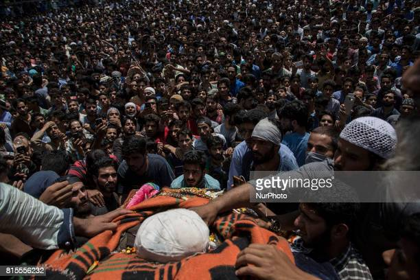 Kashmiri villagers touch the body of a local rebel Parvaiz Mir during his funeral procession Sunday July 16 in Pohoo village 38 kilometres south of...