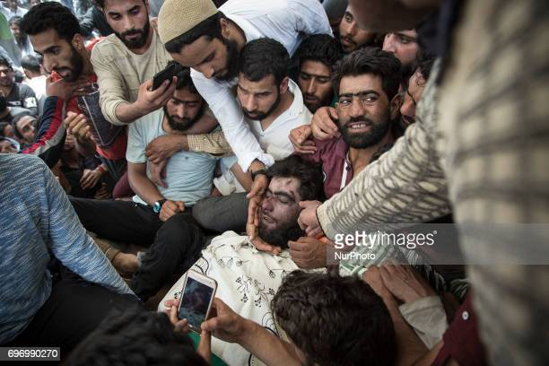 Kashmiri villagers touch the face of local rebel commander Junaid Matoo during his funeral Saturday June 17 in Khudwani village about 60 kilometers...