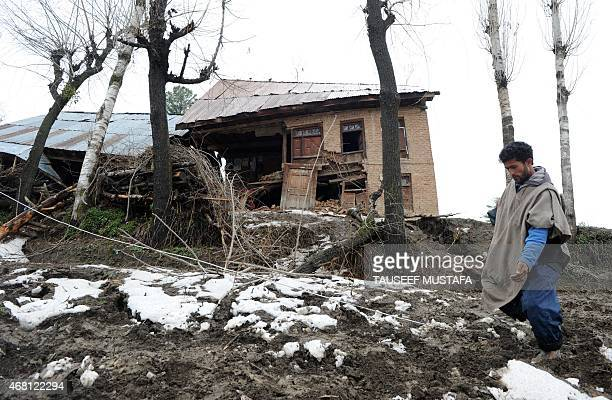 Kashmiri villagers walk near damaged houses following landslides due to heavy rainfall in the village of Laden at Chadoora some 40kms west of...