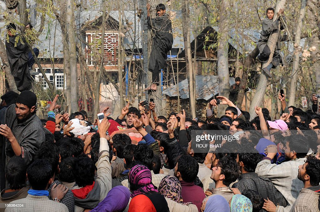 Kashmiri villagers watch as the body of suspected militant of Lashkar-e-Taiba, Shabir Ahmad is carried during his funeral procession in Chingam, some 61 kms south of Srinagar on November 14, 2012. Thousands of Muslim villagers attended the funeral of Ahmad, a suspected rebel who was killed in a gunbattle with Indian troops in the restive Kashmir. AFP PHOTO/Rouf BHAT