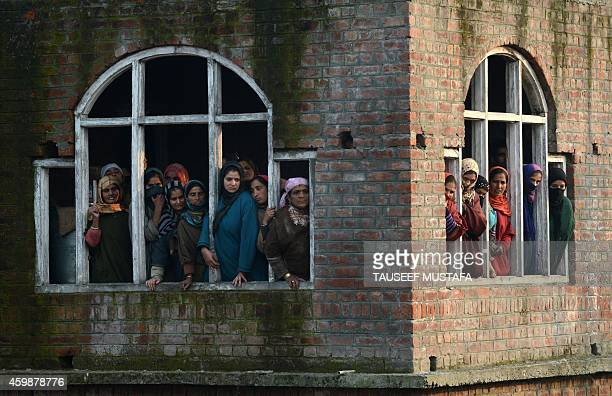 Kashmiri villagers watch during the funeral of Central Reserve Police Force trooper Mohammad Shafi Bhat at Ama Buran Pattan north of Srinagar on...