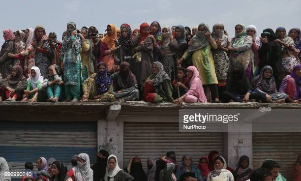 Kashmiri villagers watch the funeral procession of local rebel commander Junaid Matoo Saturday June 17 2017 in Khudwani village about 60 kilometers...