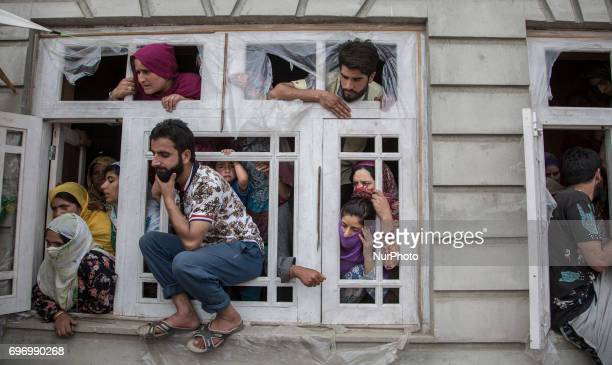 Kashmiri villagers watch the funeral procession of local rebel commander Junaid Matoo Saturday June 17 in Khudwani village about 60 kilometers south...