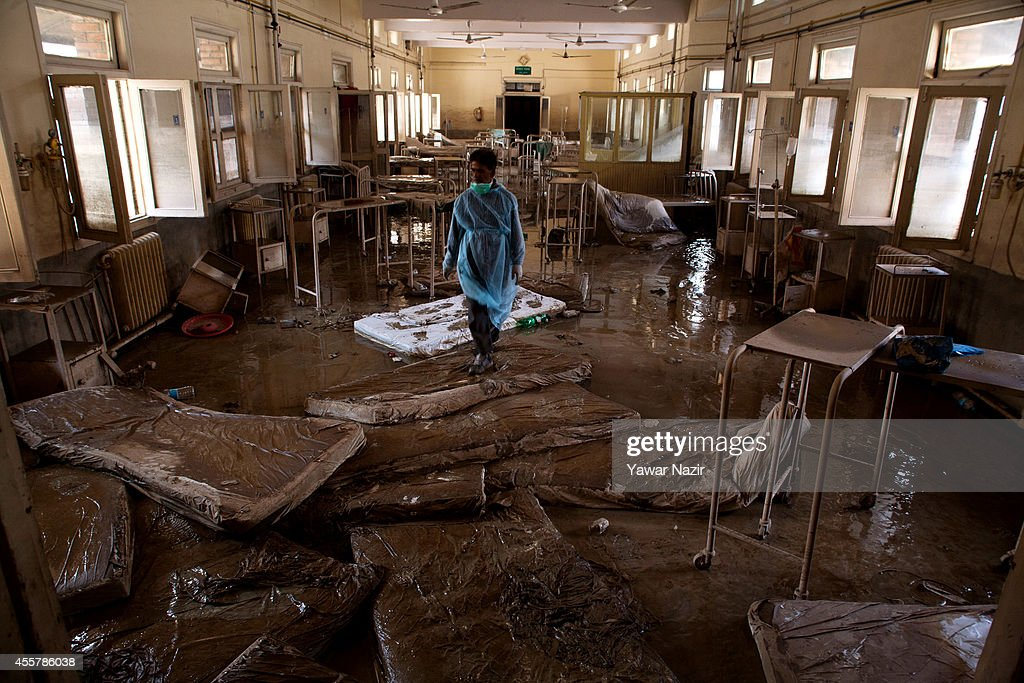 Kashmiri volunteer walks in the silt covered ward of Shri Maharaja Hari Singh Hospital after the flood waters receded from the area on September 20...