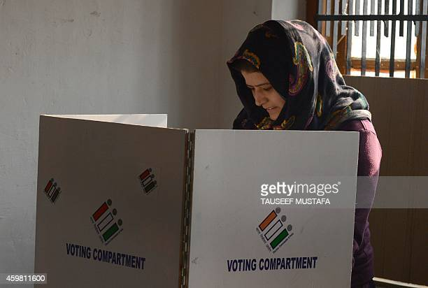 A Kashmiri voter casts her ballot at a polling station in Handwara about 70 kms north of capital Srinagar on December 2 2014 Indian Kashmir headed to...