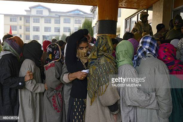 Kashmiri voters queue at a polling station in Srinagar on December 14 2014 Indiaadministered Kashmir headed to the Fourth and Final phase of state...
