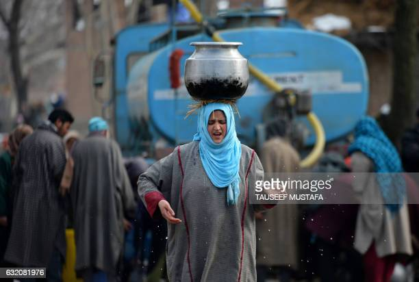 Kashmiri woman carries a water utensil filled from a water tanker on the outskirts of Srinagar on January 19 2017 The icy temperatures have frozen...
