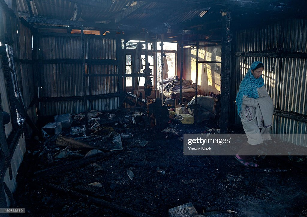 A Kashmiri woman inspects a house after a fire gutted many residential houses on December 30, 2012, in Srinagar, the summer capital of Indian administered Kashmir, India. Many families were left homeless amid sub-zero temperatures during the harshest 40-day period (Chilay Kalan) of the winter, after at least 30 residential houses were damaged in a devastating fire on the bank of famous Dal Lake near the Hazratbal shrine, in the outskirts of the Srinagar. The incident engulfed the area during the preceding night, an official said. No injuries were reported.