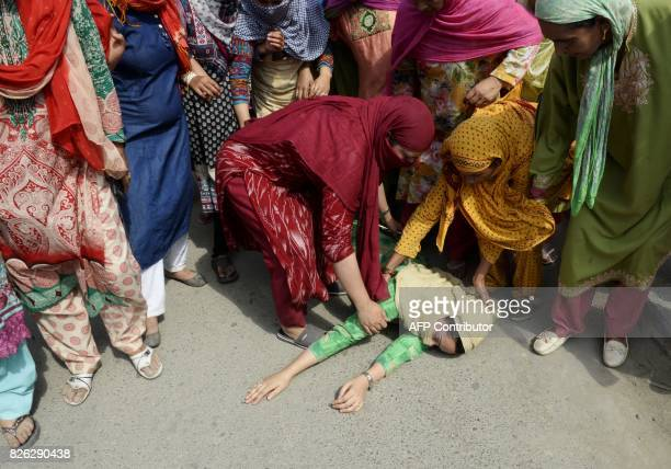 Kashmiri woman lies on the ground after fainting fainted during the funeral procession of slain militant Yawar Nissar at Shipora in Anantnag South of...