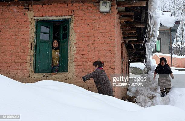 Kashmiri woman looks out of the window as children play in Tanmarg about 34 kms north of Srinagar following a fresh snowfall on January 18 2017 / AFP...
