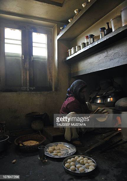A Kashmiri woman makes a local bread ''Roti'' using a traditional owen on the outskirts of Srinagar on December 16 2010 Though a large number of...
