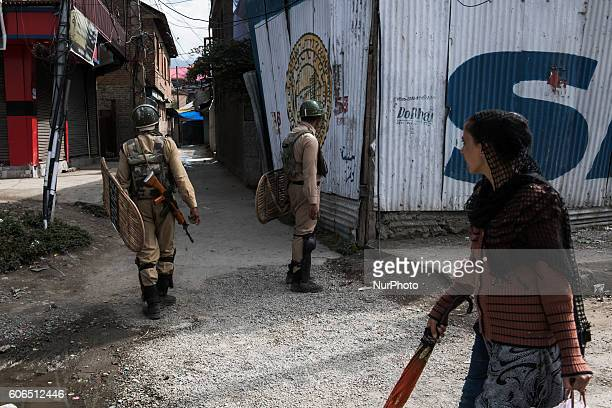 A Kashmiri woman passes by security forces making a strict search for stone pelters after a clash with protestors in Naupura Srinagar Kashmir 31...