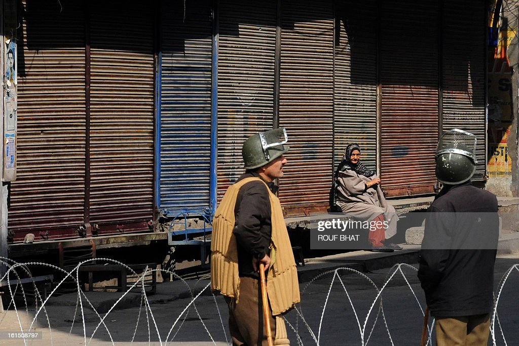 A Kashmiri woman (C) sits beside shuttered shops as Indian policemen keep watch on the fourth day of a curfew in Srinagar on February 12, 2013. Security forces have imposed a curfew in much of Indian Kashmir following the execution February 9 of Mohammed Afzal Guru, convicted of helping to plot the deadly 2001 attack on the Indian parliament, while a general strike was in force on Monday to mark the 29th anniversary of the execution of Maqbool Bhat, a leader of the Jammu Kashmir Liberation Front (JKLF). AFP PHOTO/Rouf BHAT