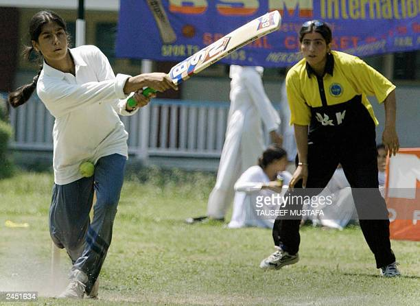 A Kashmiri woman student receives a ball to the body as the wicket keeper of the opposing team looks on during the final match of womens tennis ball...
