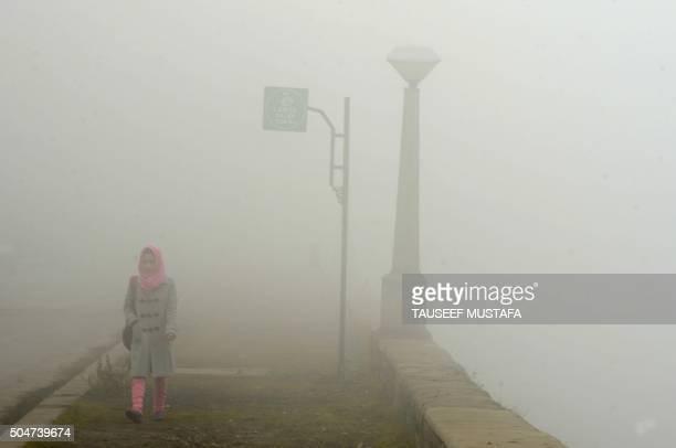 Kashmiri woman walks along the banks of Dal lake during dense fog in Srinagar on January 13 2016 / AFP / TAUSEEF MUSTAFA