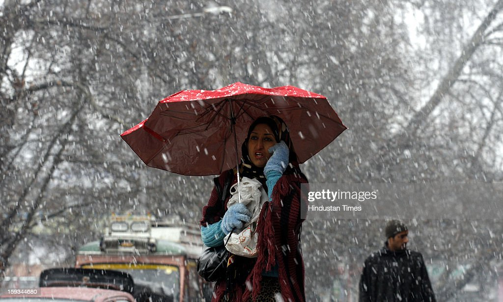 Kashmiri woman walks during a fresh snowfall on January 12, 2013 in Srinagar, India. The Kashmir Valley experienced fresh snowfall today, forcing authorities to close the Srinagar-Jammu highway.