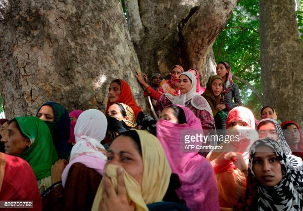 Kashmiri woman watch the funeral procession of slain rebel Abid Ahmed in the village of Hajinar in the district Bandipora north of Srinagar on August...