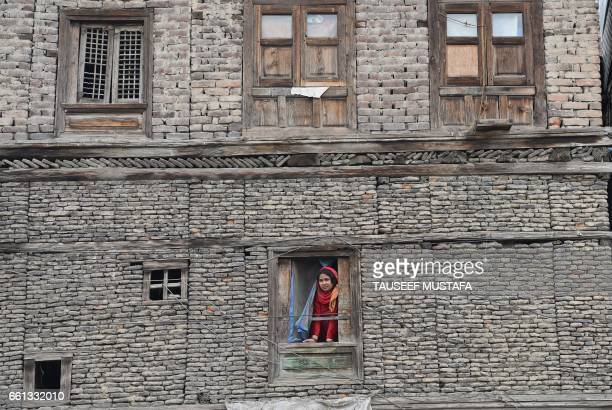 Kashmiri woman watches from the window of a house as unseen senior seperatist leader MushtaqulIslam shouts profreedom slogans during a protest...