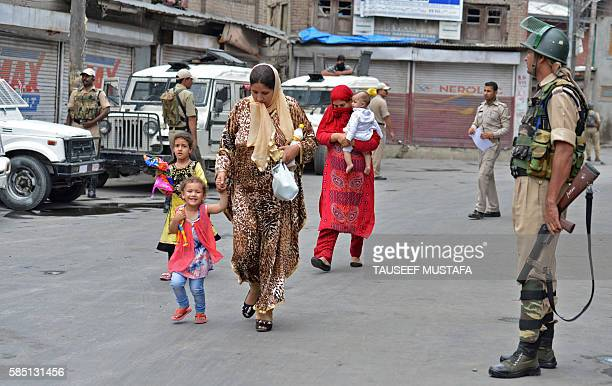 Kashmiri women and children walk past Indian paramilitary troopers on a street in Srinagar on August 2 2016 More than 50 people have been killed and...