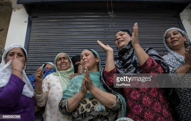 Kashmiri women grieve as they watch the funeral procession of local rebel Adil Ahmed Saturday June 17 on the outskirts of Srinagar Indianadministered...