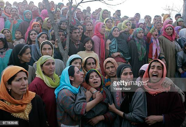 Kashmiri women look towards the dead body of Khursheed Ahmad a salesman who was killed in a shoot out between Indian Police and suspected militants...