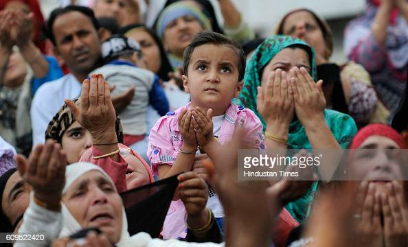 Kashmiri women pray as a head priest displays a holy relic believed to be the hair from the beard of the Prophet Muhammad at the Hazratbal Shrine on...
