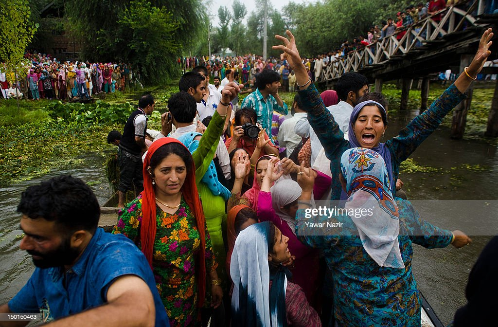 Kashmiri women shout anti government slogans as Volunteers and rescuers search for survivors in the water after a footbridge collapsed into the water on August 11, 2012 in Srinagar, the summer capital of Indian administered Kashmir, India. According to witnesses and locals many people were injured some of them critically after an old makeshift foot bridge partially crumbled down due to overweight, in the interiors of Dal Lake .