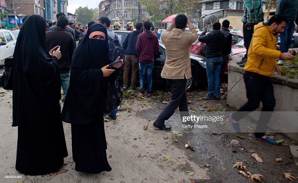 Kashmiri women take pictures of damaged cars hit by a tree branch after a powerful earthquake struck northern Afghanistan with tremors felt as widely...