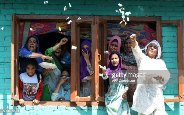 Kashmiri women throw candies during the funeral procession of slain rebel Abid Ahmed in the village of Hajin in the district Bandipora north of...