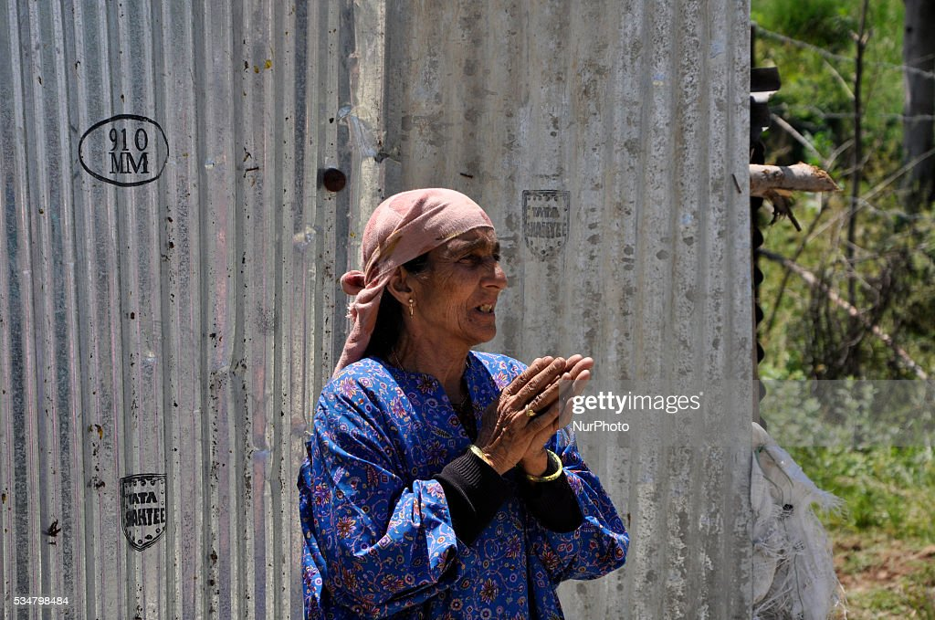 A kashmiri women wails as she looks towards the encounter spot where the two rebels were killed site in Khonshipora 25 miles west of srinagar on May 27,2016.Two rebels were killed by indian forces during a brief gunfight
